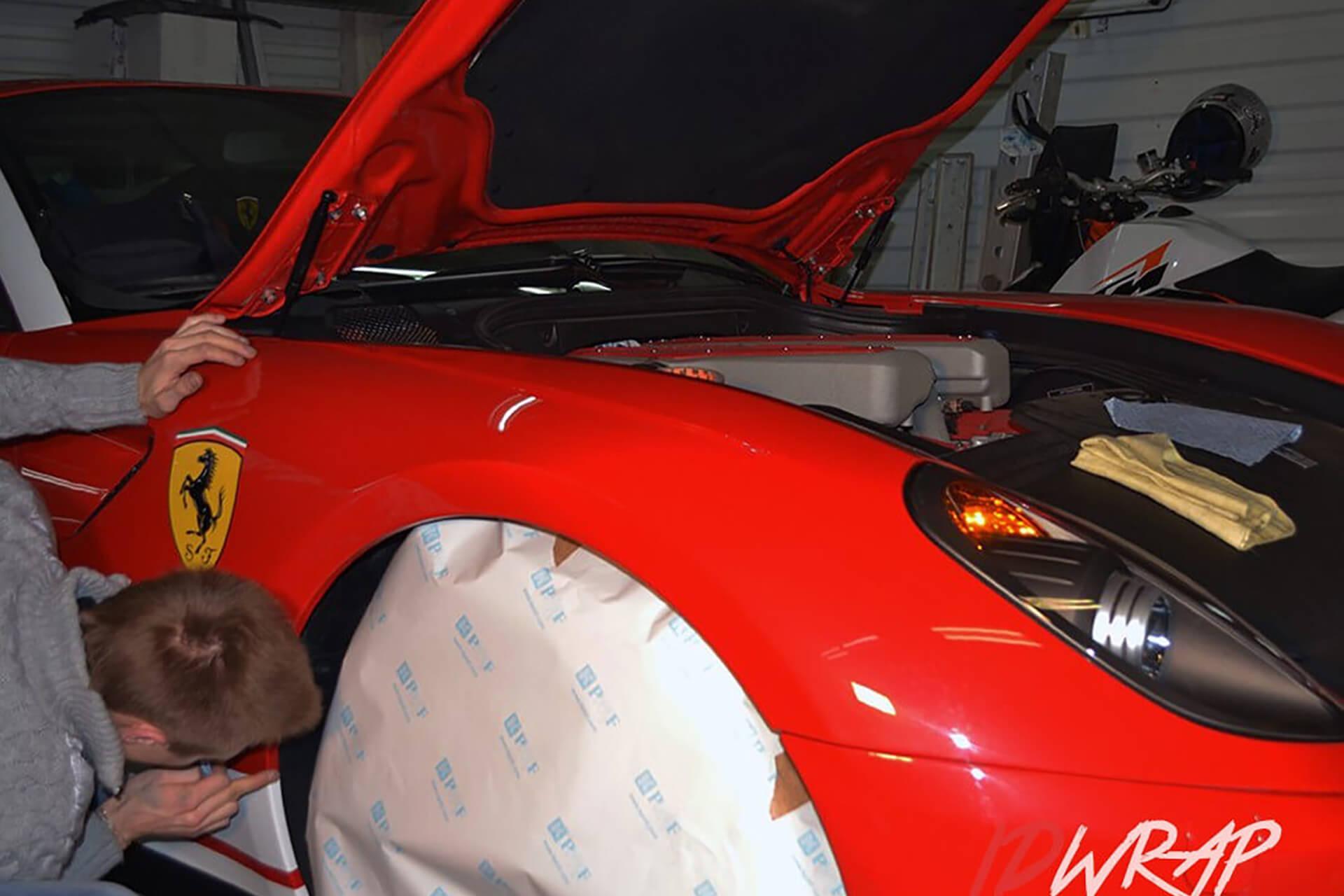 Красный Ferrari в глянцевой пленке